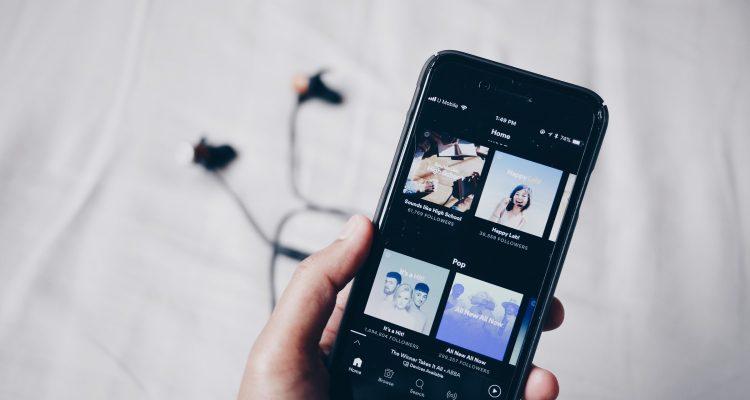 Hand hält Smartphone mit Kopfhörern