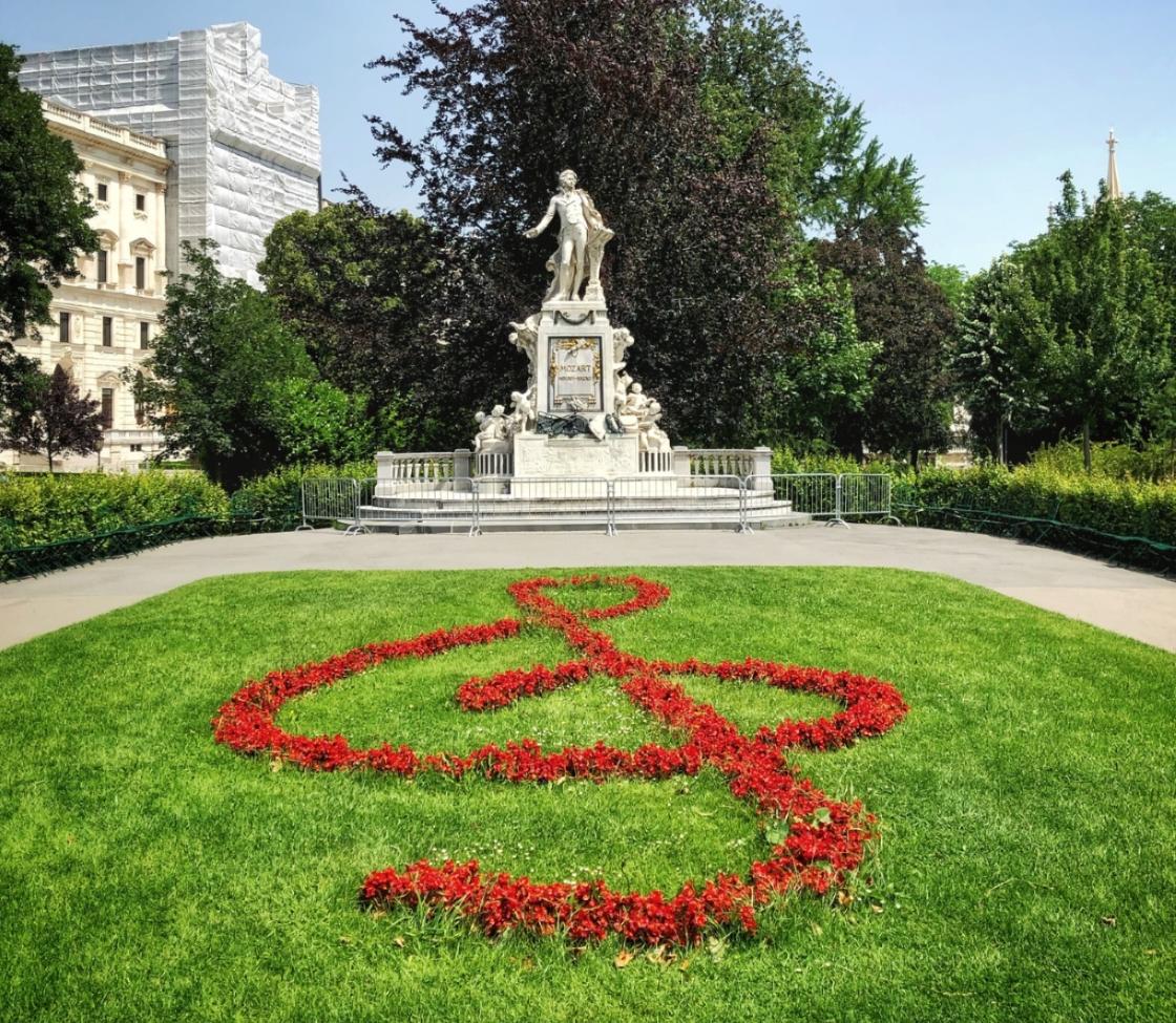 Statue vor einer Wiese auf der Blumen einen Notenschlüssel nachbilden.