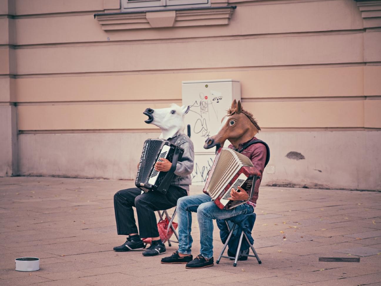 Zwei Akkordeospieler auf der Straße mit Pferdekopfmaske.