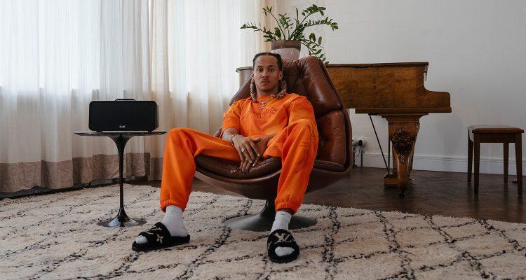 Kelvyn Colt in einem Sessel sitzend mit Lautsprecher BOOMSTER von Teufel